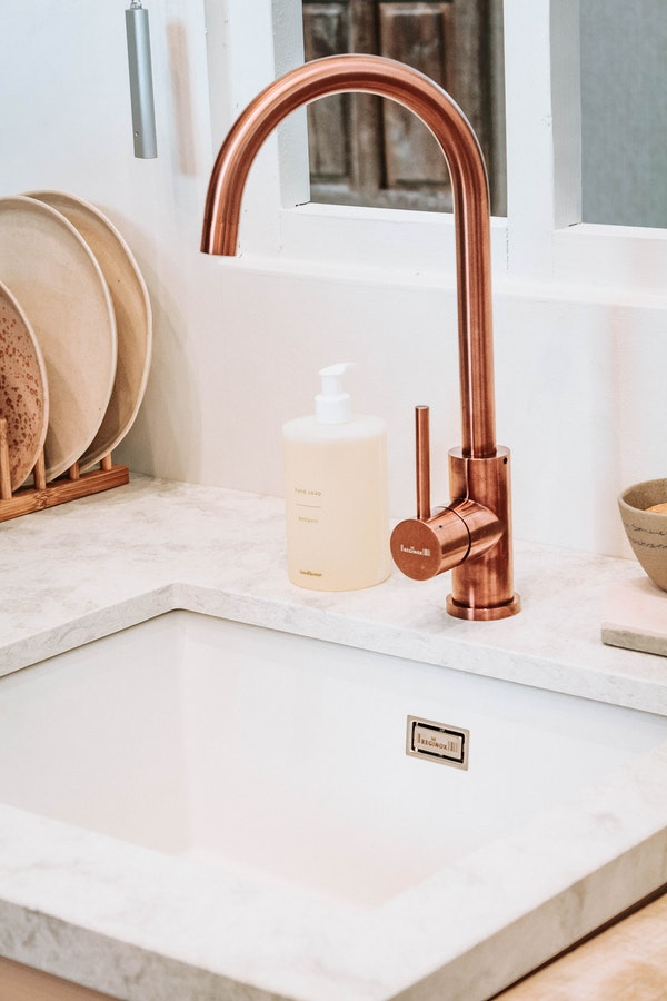 copper-faucet-in-kitchen-with-undermounted-sink-and-handsoap-container