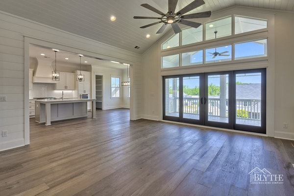 Living Room with shiplap wall and shiplap vaulted ceiling and rustic hardwood floors