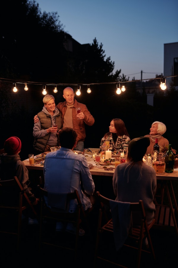 family-Thanksgiving-celebration-outside-with-string-lights-at-night