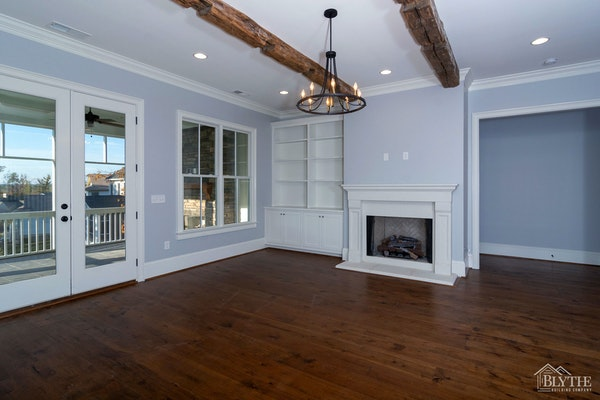 white fireplace surround with white tile facing, painted fireplace wall, and a built-in cabinet/bookshelf on one side.