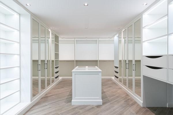 Luxury walk-in closet with closet island, white shelves, white drawers, and mirror closet doors