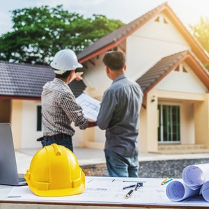 Contractor and client standing in frontof a home under construction with table with hardhat and blueprints in the foreground.