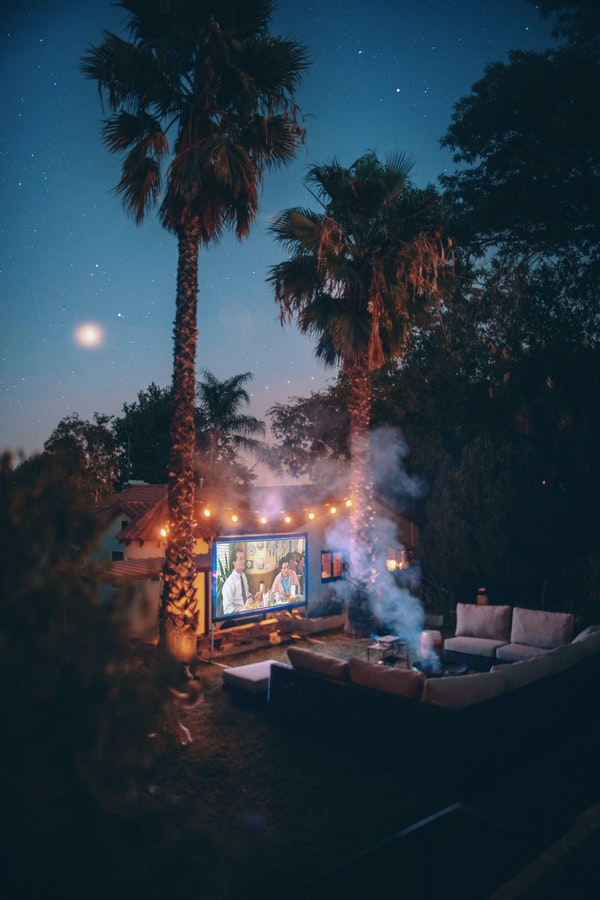 Patio at night with patio string lights, fire pit, and movie screen and palm trees and moon and stars