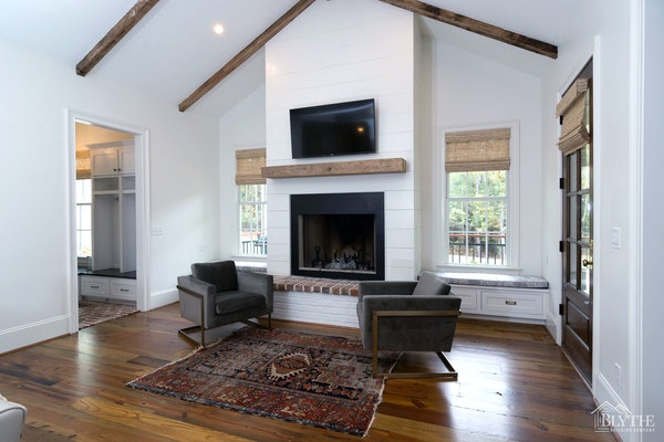 a shiplap fireplace wall, wood mantel, and painted brick hearth with custom window seats beside fireplace