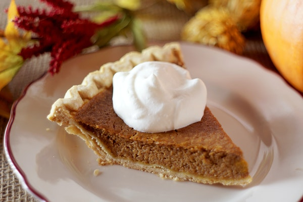 pumpkin-pie-slice-with-cool-whip-on-fine-china-plate