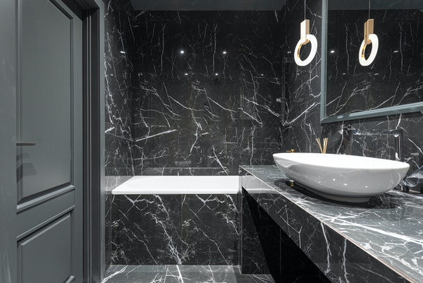 Black marble bathroom with marble walls, marble floor, and marble countertop