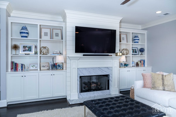 White fireplace surround with columns and a crown molding shelf with an inner marble fireplace surround, and floor-level hearth and shiplap fireplace wall.