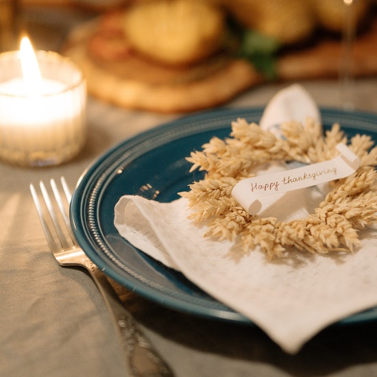 Thanksgiving-place-setting-with-blue-plate-white-cloth-napkin-wreath-and-candle