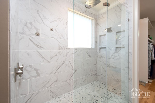 Oversized Shower with marble tile In Luxury Master Bathroom With Tile Walls And Tile Mosaic Floor And Two Shower Heads 1
