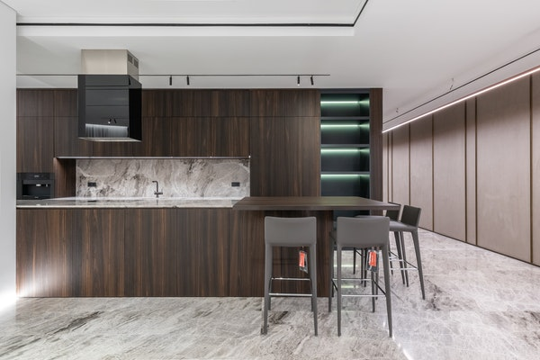 Contemporary kitchen with marble backsplash, marble floors, and dark cabinets