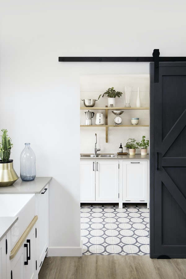 Kitchen in the foreground and a sliding barn door to a scullery in the background