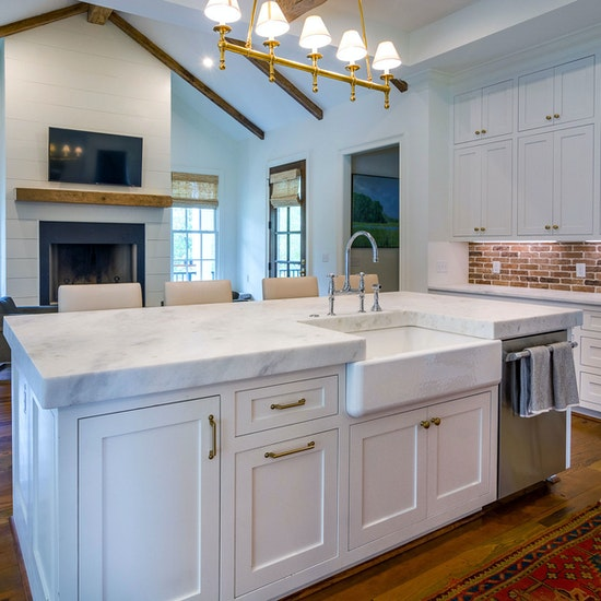 White kitchen with marble countertop on island and real brick tile backsplash