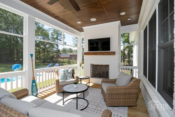 Beadboard ceiling on screened-in back porch with tv and outdoor fireplace