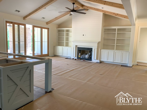 Great room under construction with ceiling beams and built-in cabinets