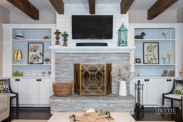 Stacked stone veneer fireplace surround with white crown molding mantel and built-in bookcases on each side of the fireplace with a shiplap fireplace wall