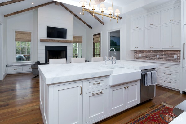 Kitchen with vaulted ceiling, white shaker cabinets, farmhouse sink, and brick backsplash