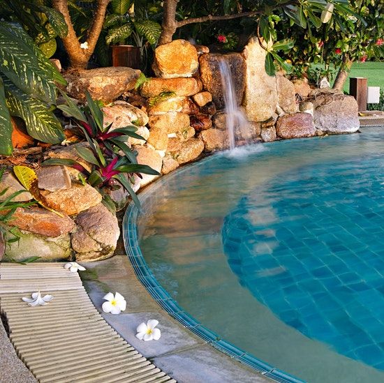 Beautiful luxury pool for your custom home with waterfall feature, blue tile, and tropical plants