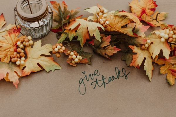 thanksgiving-table-decorations-with-fall-leaves-candle-and-words-give-thanks