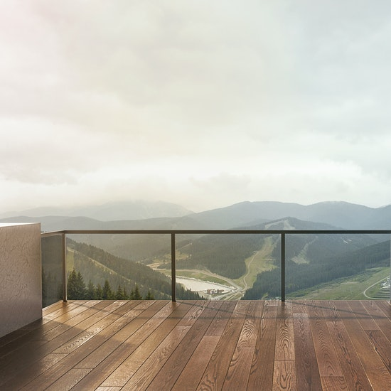Tropical hardwood custom deck with glass railing overlooking mountains