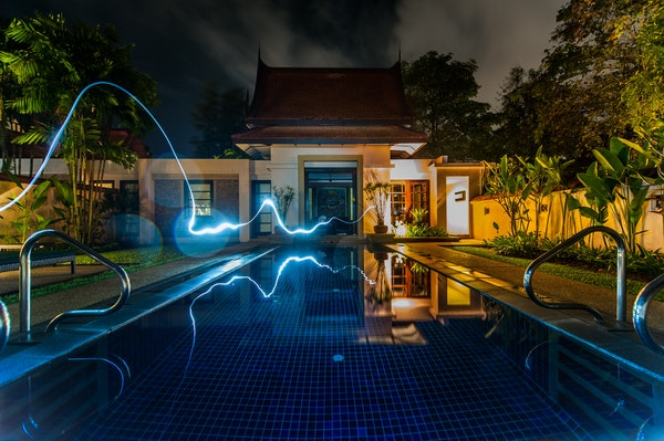 Luxury-home-at-night-with-pool-and-glowing-line-of-electricity-going-to-house.jpg