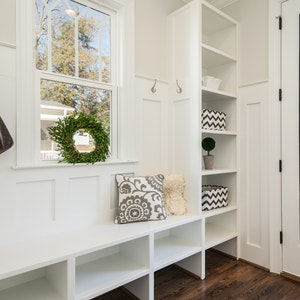 White mudroom with built-in cabinets, cubbies, and hardwood floors