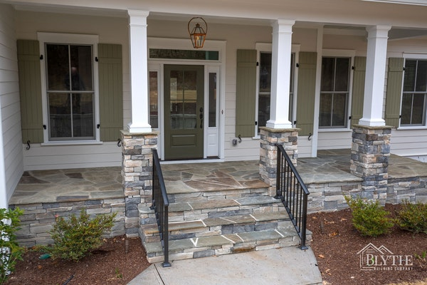 Front Porch With Half Stacked Stone Columns and Green Board and Batten Shutters