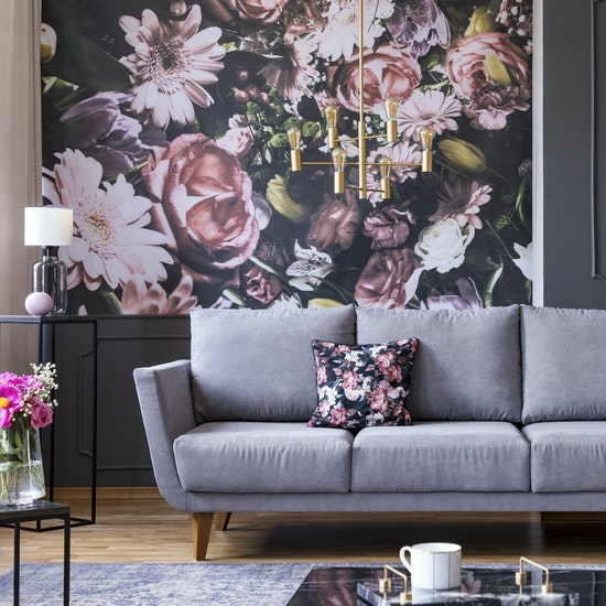 Maximalist design with wallpaper accent wall, couch, and throw pillow