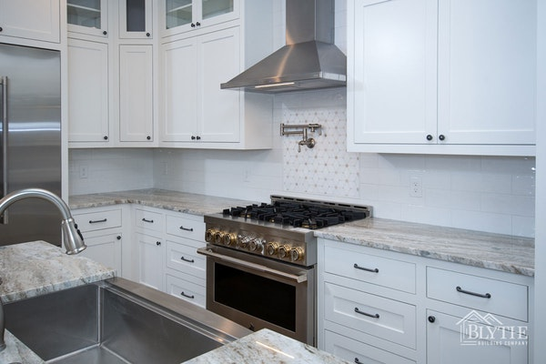 Modern Craftsman Kitchen With Long White Subway Tile White Shaker Cabinets  and Fantasy Brown Quartzite Counters Gas Range And Stainless Steel Industrial Range Hood