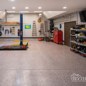 Custom 4-Car Garage With Vaulted Ceiling And Car Lift, a true dream garage.