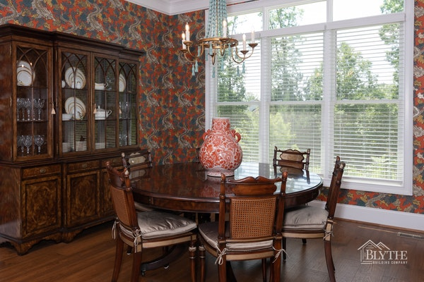 Dining room with bold red dragon motif wallpaper and hardwood floors