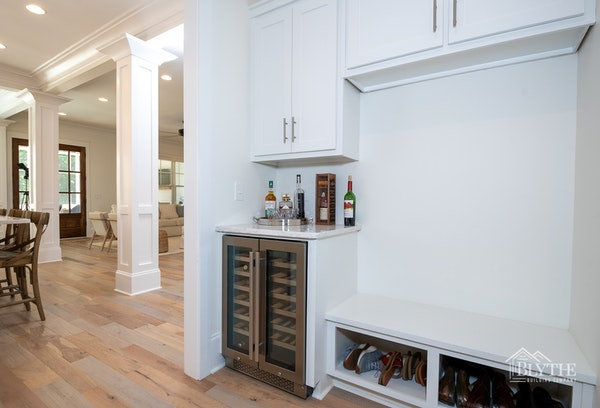 Mudroom with white built-in bench seat and wine cooler near kitchen