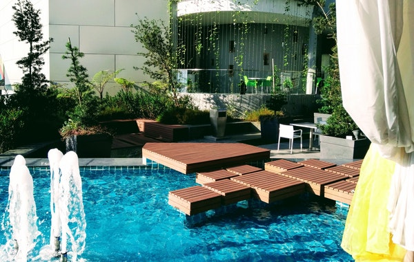 custom deck built over a pool and water fountain feature
