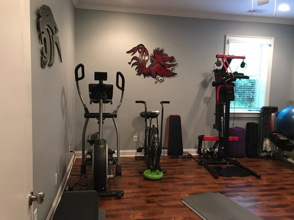 Custom home gym with stationary bike and weight machine and hardwood floors