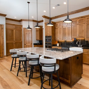 Stained maple wood cabinets and hickory wide planked floors in a luxury kitchen