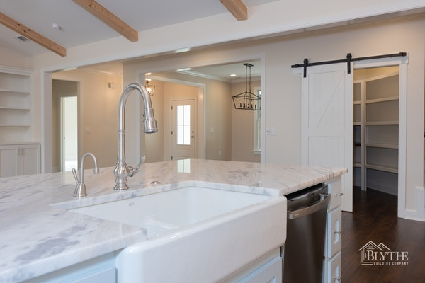farmhouse-kitchen-sink-and-barn-door-with-panty-and-ceiling-beams.jpg