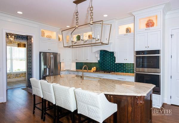 Luxury kitchen with white cabinets, green tile backsplash, and large pendant light