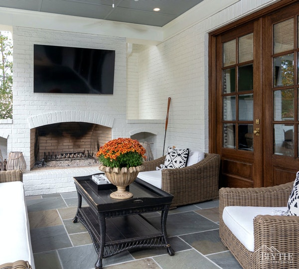 back porch with masonry fireplace and outdoor TV with living space