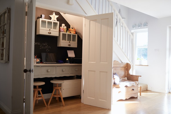 Entryway office in a closet with white doors and white built-in desk