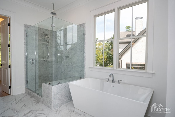 Large custom marble tile shower with glass enclosure and sculpted stand-alone tub