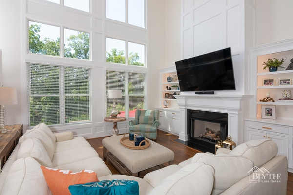 two-story ceiling living room with molding on the wall over the fireplace
