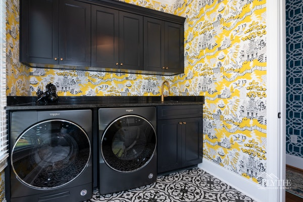 Maximalist design laundry room with wallpaper and patterned floor tile