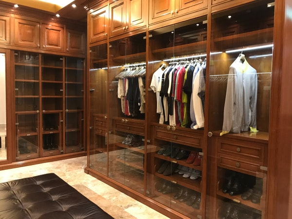 Hardwood and glass luxury closet with black cushioned ottoman and LED lighting