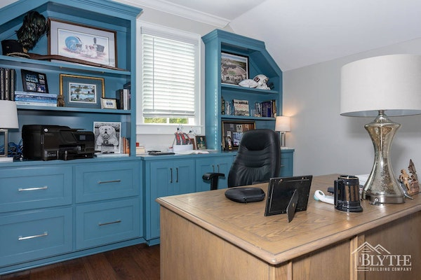 Custom office with blue built-in shelves and book cases