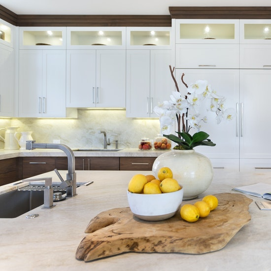 White kitchen cabinets with under-cabinet lighting and staging