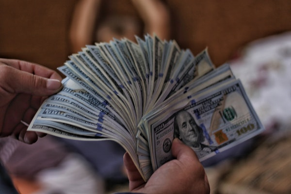Person's hands fanning many $100 US dollar bills.