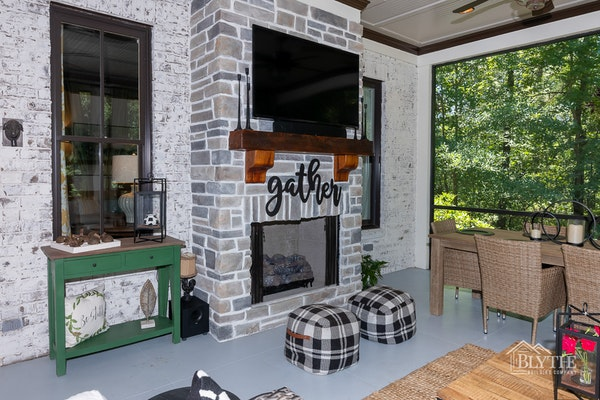 Screened-in back porch with outdoor fire place and outdoor TV
