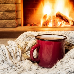 Cozy fireplace with roaring fire and a blanket with a cup of hot cocoa in the foreground.