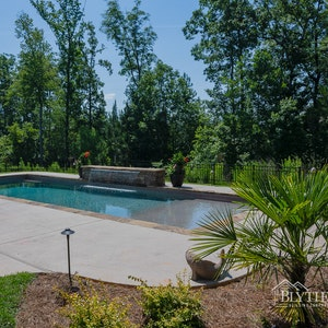 Large in-ground custom swimming pool with 8 ft long waterfall feature