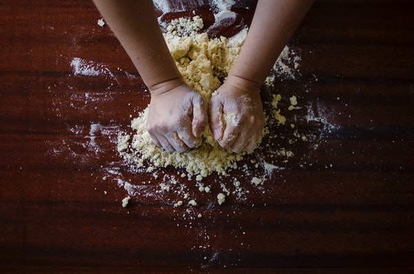 Hands kneading dough on a wooden countertop
