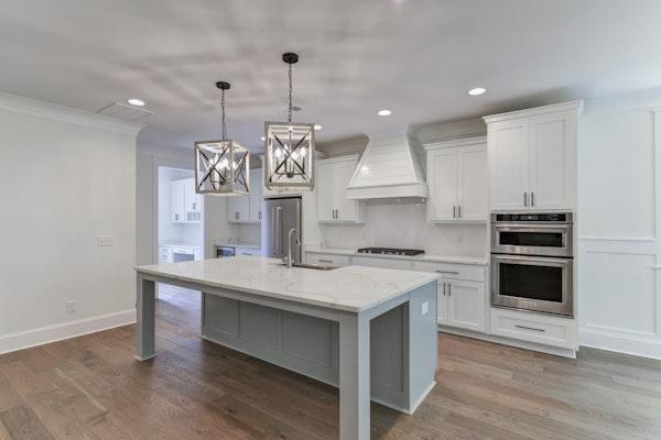 Luxury Kitchen With White Shaker Cabinets and Shiplap Range Hood